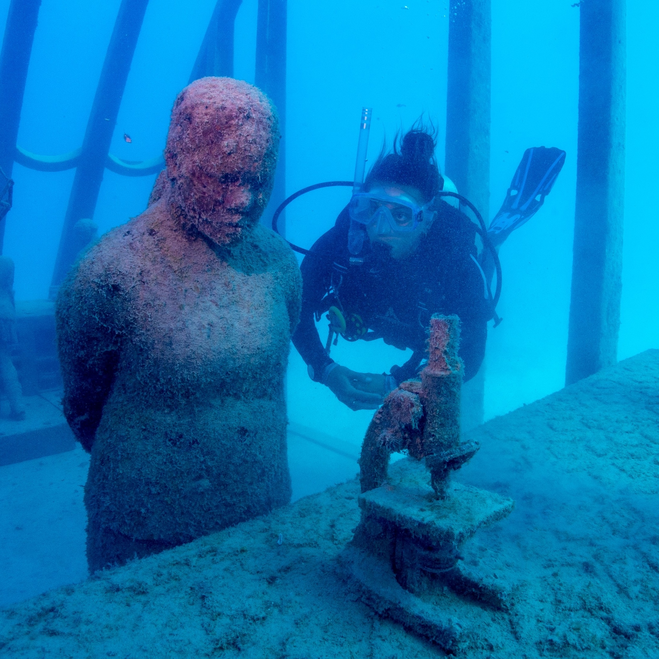Scuba diver swims next to a statue inside the Coral Greenhouse at the Museum of Underwater Art © Gemma Molinaro Photographer