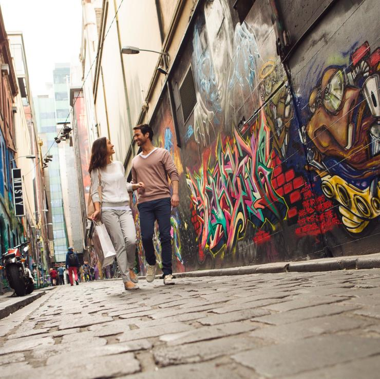 Couple walks through graffitied Hosier Lane in Melbourne © Tourism Australia