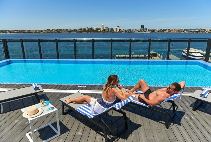 Couple sunbathe by rooftop pool at DoubleTree by Hilton Waterfront, Perth, Western Australia © DoubleTree by Hilton Perth Waterfront