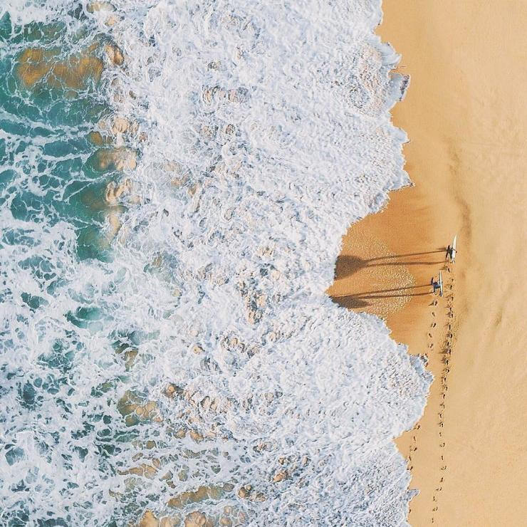 Aerial overlooking surfers walking along Palm Beach, Sydney © Adam Krowitz