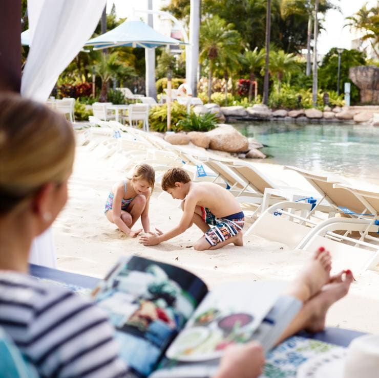Women reading magazine relaxes by the pool at Surfers Paradise Marriott Resort & Spa © Surfers Paradise Marriott Resort & Spa