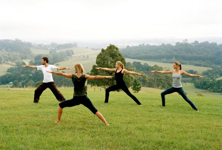 Students taking a yoga class on the grass at Gaia Retreat and Spa in Byron Bay © Tourism Australia