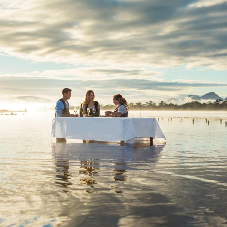 Three people stand in the water at a table tasting oysters at Saffire Freycinet Marine Oyster Farm in Tasmania's Coles Bay © Saffire Freycinet/Tourism Tasmania