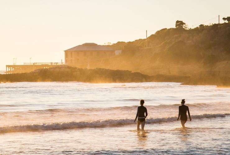 Two people walk into the ocean at sunset at Tathra Beach in New South Wales © Destination NSW