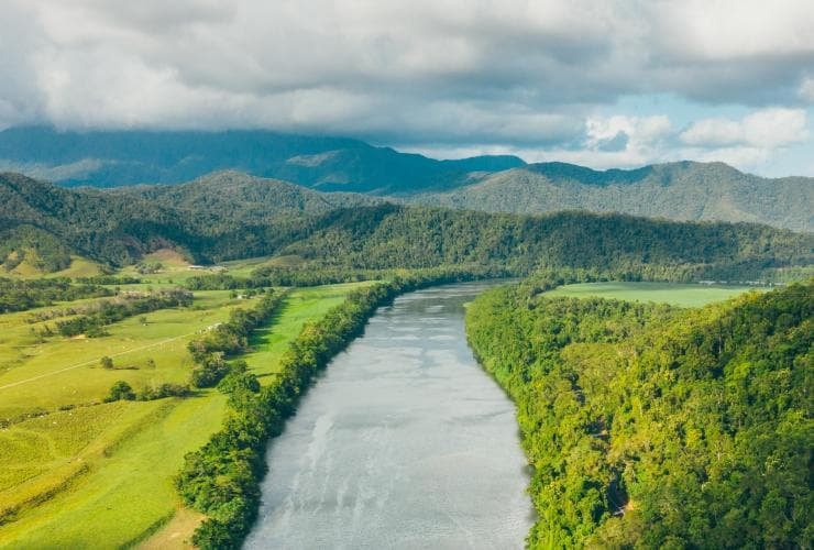 A wide, calm river runs through the bright green Daintree Rainforest © Tourism and Events Queensland