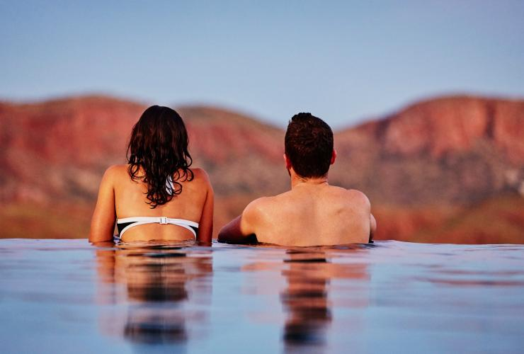 Couple enjoys the view of mountains from an infinity pool at Lake Argyle Resort © Tourism Western Australia