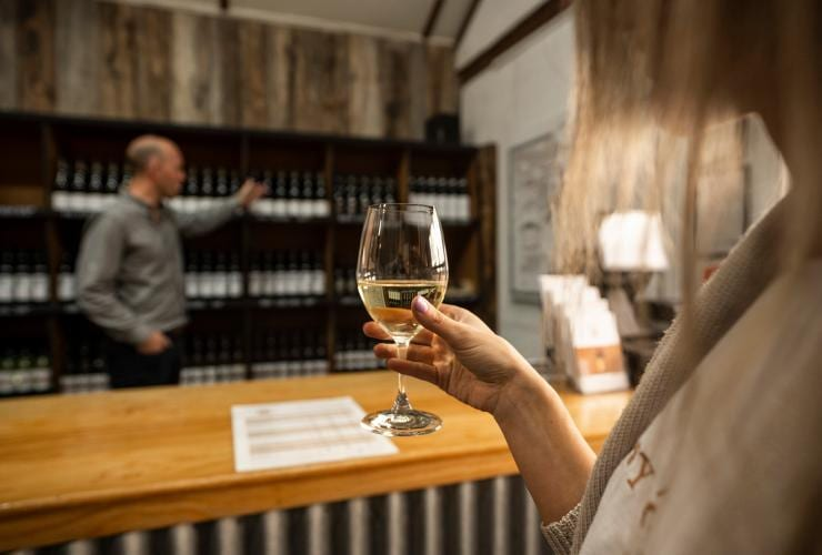 Woman holding a glass of white wine during a wine tasting at Tyrell's Wines © Rob Mulally
