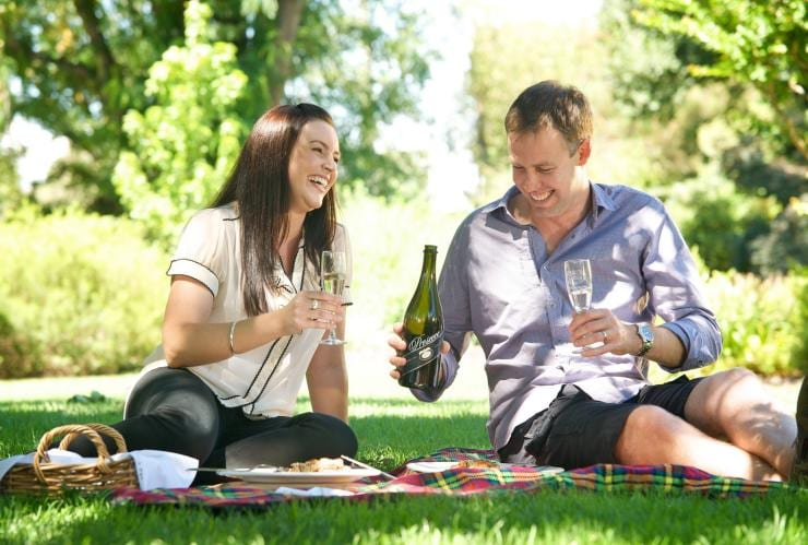 Couple enjoying prosecco at a picnic at Brown Brothers Winery © Visit Victoria