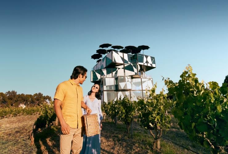 Couple with picnic basket in front of the d'Arenberg Cube in McLaren Vale © Tourism Australia