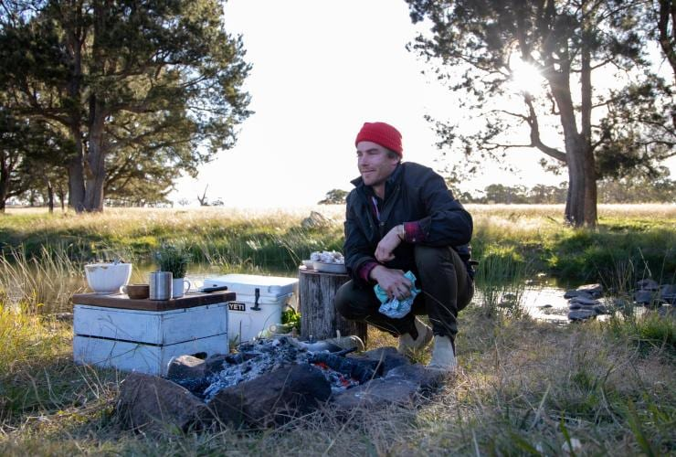 Chef Hayden Quinn sits near campfire in New England © Boomtown Pictures