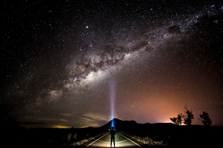 Stargazer with a head torch looking up at the milky way © Tourism and Events Queensland/Sean Scott