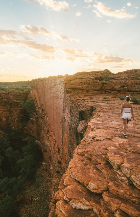 A woman walking on top of Kings Canyon at sunrise © Tourism NT/Mitchell Cox 2017
