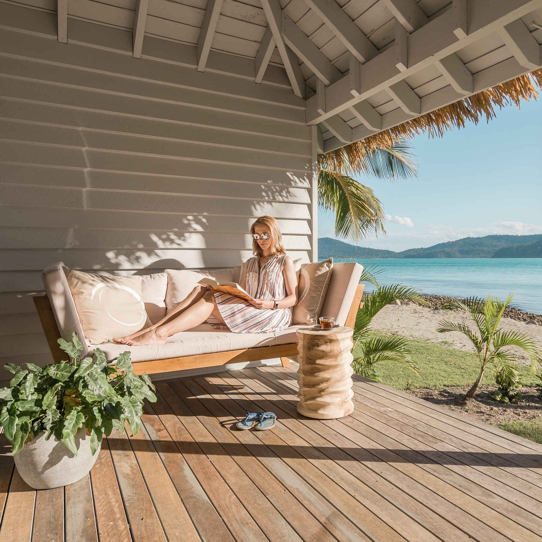 Woman reads book on balcony by ocean at Elysian Retreat © Elysian Retreat/Nathan White