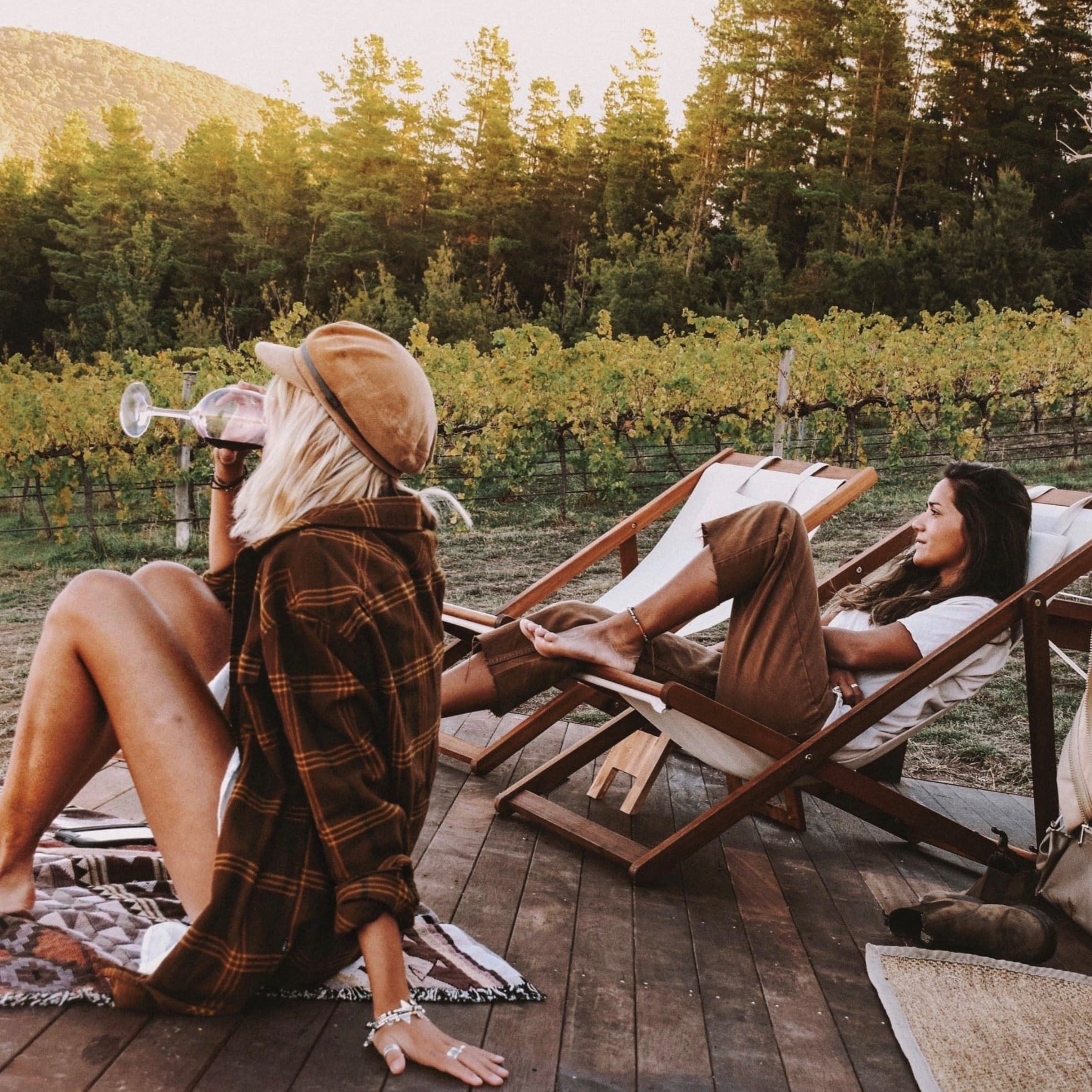 Women drink wine outside glamping tent at Naked Cubby Co near Canberra © Naked Cubby Co/Shan Bawden