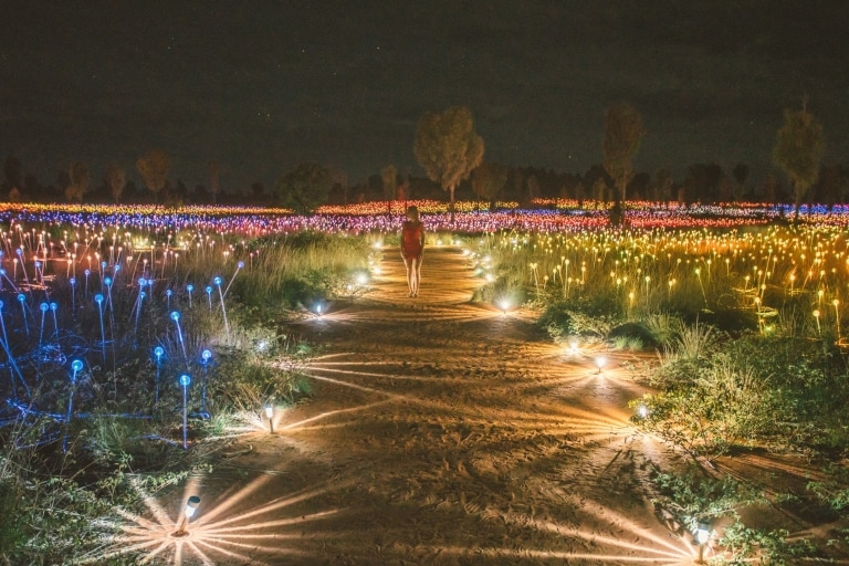 A visitor walking through the Field of Light art installation © Tourism NT/Mitchell Cox