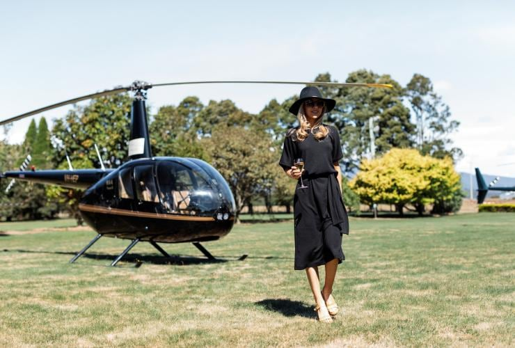 Woman with a glass of wine in front of a helicopter of Clover Hill Winery in Lebrina © Clover Hill