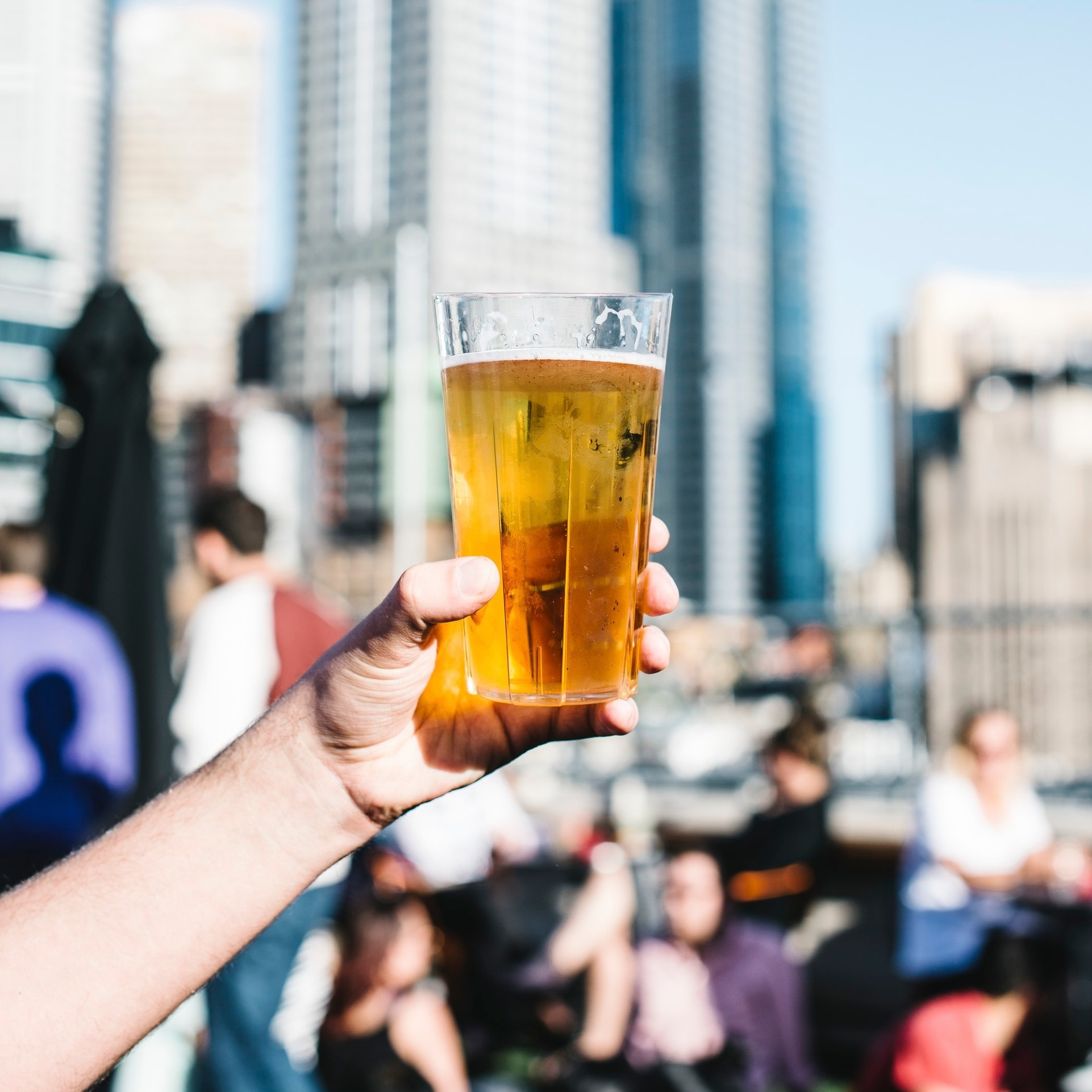 Hand holding a pint of beer at a rooftop bar in Melbourne © Tourism Australia