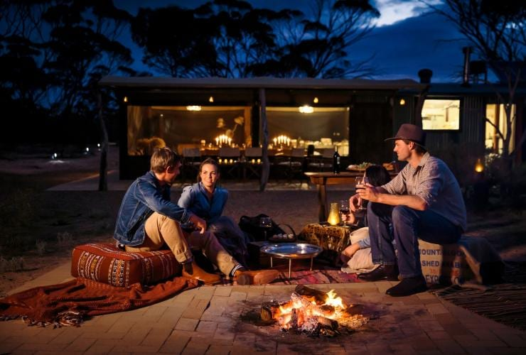 Friends sit around a campfire at Kangaluna Camp in the Gawler Ranges © South Australian Tourism Commission