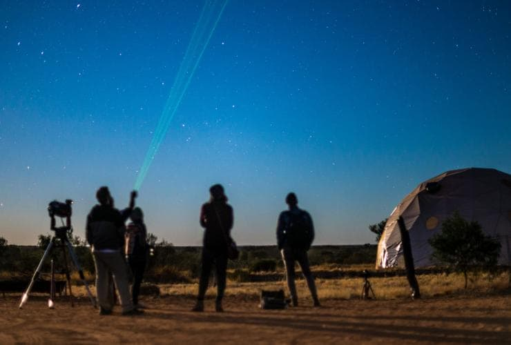 Silhouettes of people gazing at the stars at Earth Sanctuary World Nature Centre © Tourism NT/Shaana McNaught