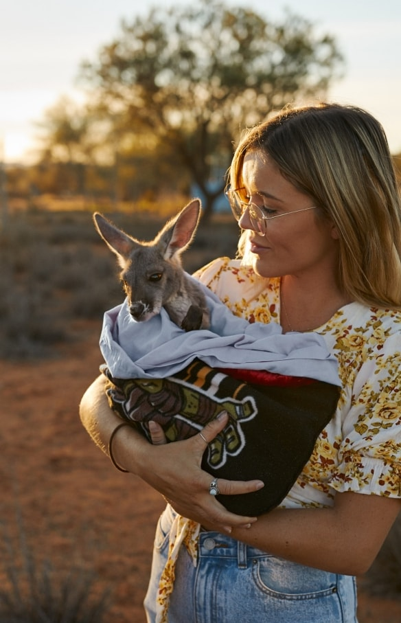 Menggendong Bayi Kanguru di The Kangaroo Sanctuary di Alice Springs di Northern Territory © Tourism NT/Matt Cherubino 2019