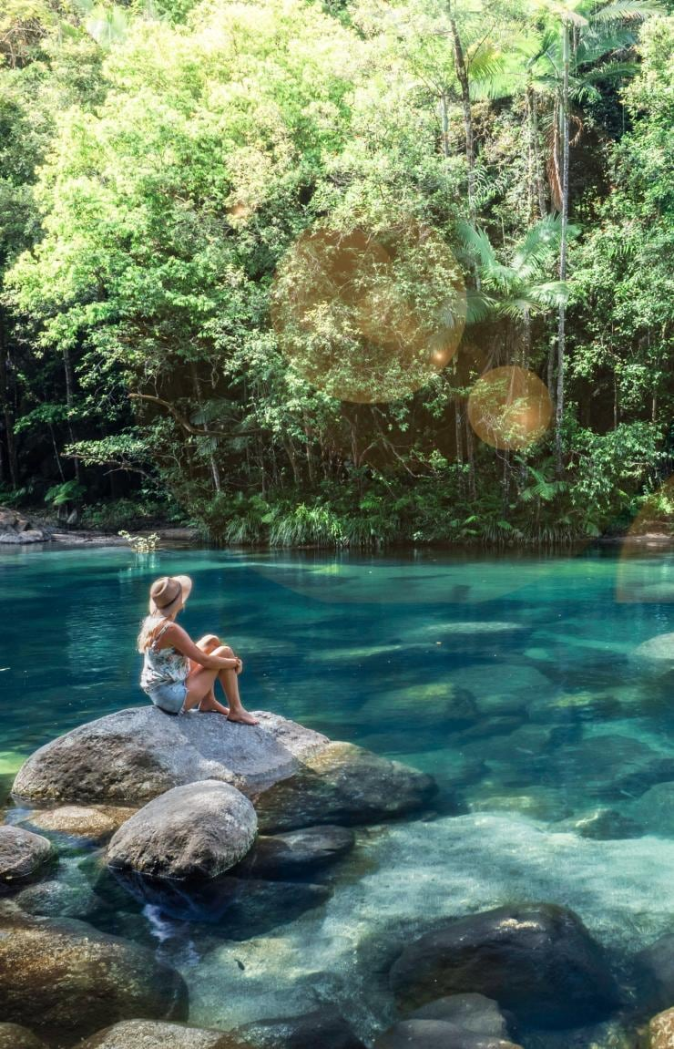 Donna seduta sulla roccia accanto a una piscina naturale di Mossman Gorge © Tourism and Events Queensland