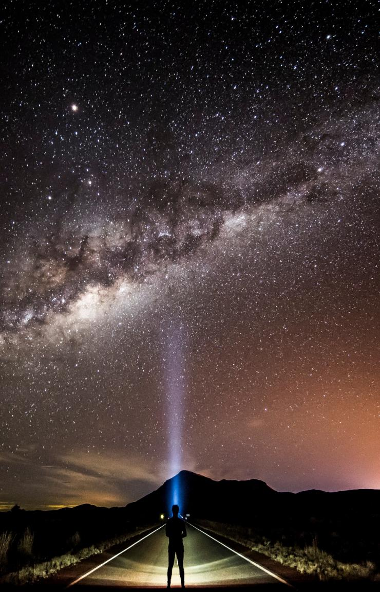 Visitatore intento ad ammirare le stelle della Via Lattea con una torcia © Tourism and Events Queensland/Sean Scott