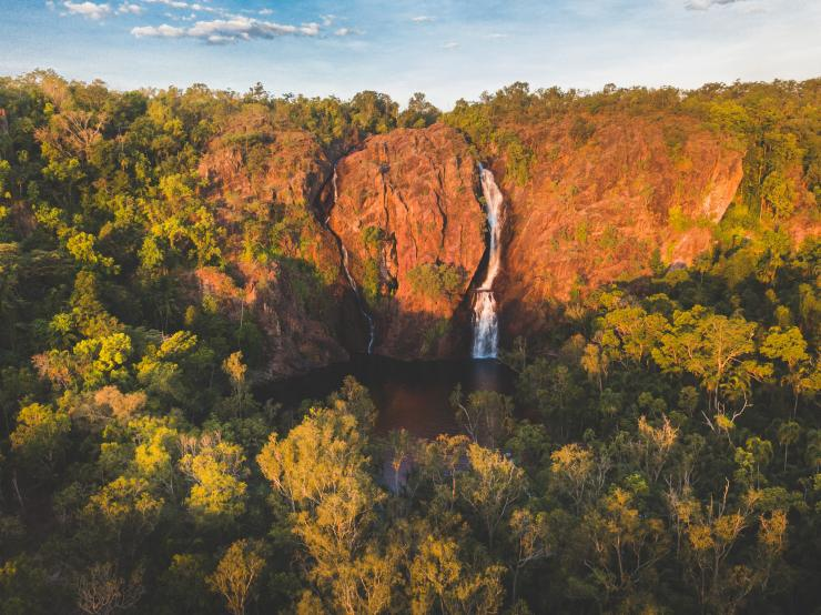 An aerial view of Wangi Falls against a red rock cliff in Litchfield National Park © Tourism NT/Dan Moore