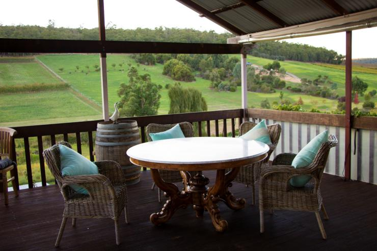 A dining table overlooking green pastures © Bickley Valley Cottage