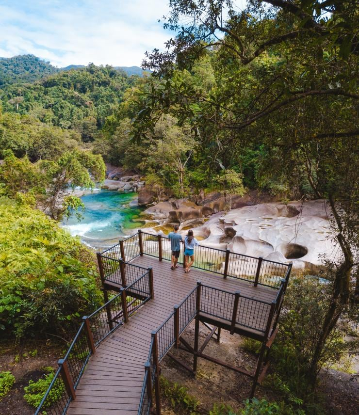 Visitors stand on a platform overlooking a natural spring © Tourism and Events Queensland