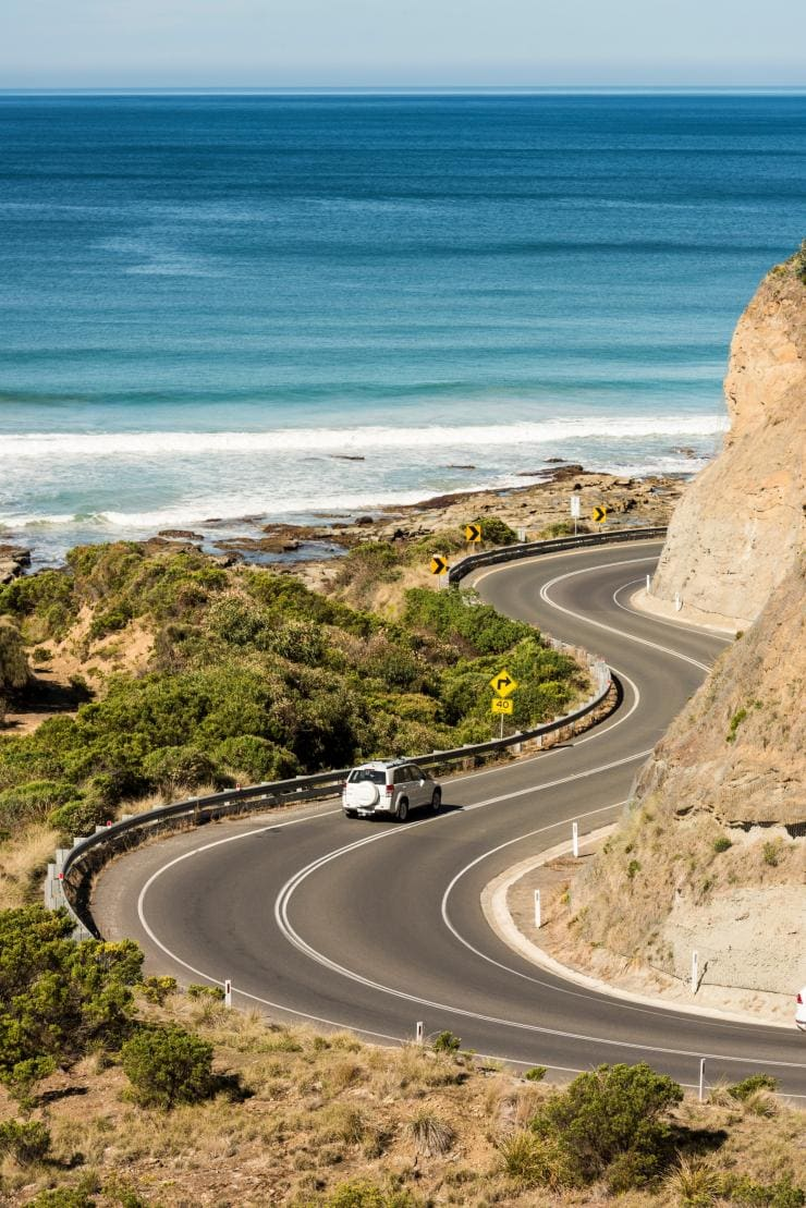 Car drives along the winding Great Ocean Road © Visit Victoria